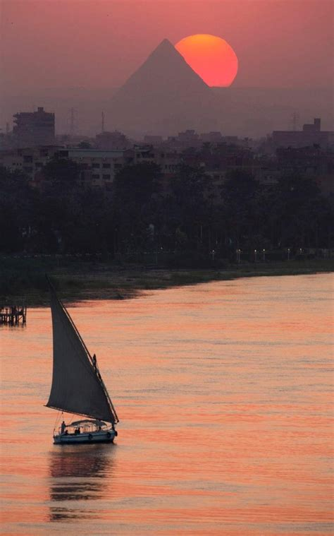 The sun sets over the historical site of the Giza Pyramids